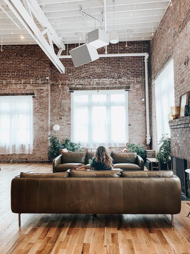Kobieta siedząca na kanapie w salonie na tle okna zasłoniętego roletą